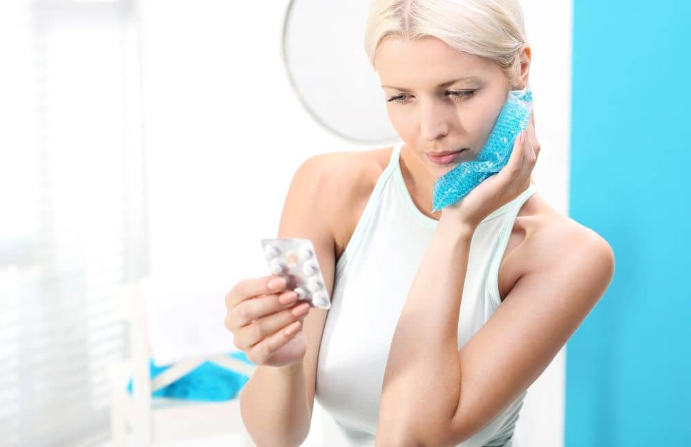 Woman applying cold compress to cheek and taking medication.